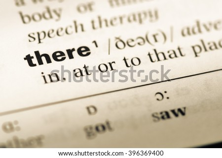 Close up of old English dictionary page with word there - stock photo
