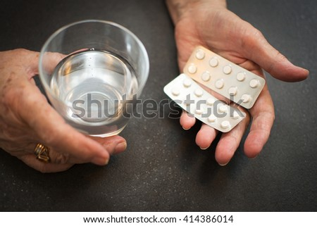 Close up of old hands with tablets and a glass of water. - stock photo