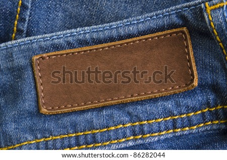 Close-up of old leather tag with copy space, sewed on blue jeans back - stock photo