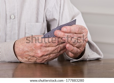 Close up of old man hands holding cards in game on table - stock photo