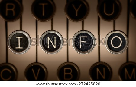 "Close up of old manual typewriter keyboard with scratched chrome keys that spell out ""INFO"". Lighting and focus are centered on ""INFO"" keys. 
