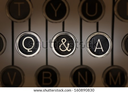 """Close up of old manual typewriter keyboard with scratched chrome keys that spell out """"Q & A"""". Lighting and focus are centered on """"Q & A"""" keys.  - stock photo"""