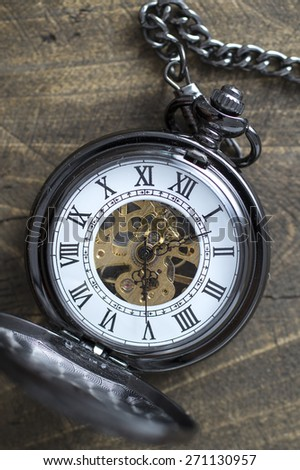 Close up of old pocket watch on rustic wooden background