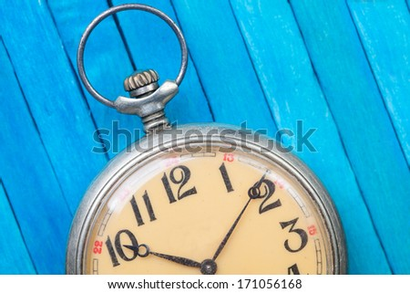 close up of old style pocket watch on blue wooden back?round - stock photo
