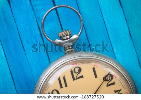 close up of old style pocket watch on blue wooden background - stock photo