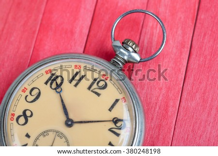 close up of old style pocket watch on red wooden background - stock photo