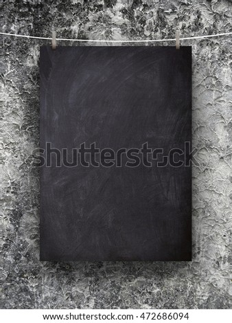 Close-up of one blank blackboard frame hanged by pegs against gray old weathered concrete wall background