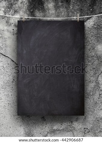 Close-up of one blank blackboard frame hanged by pegs against gray scratched wall background