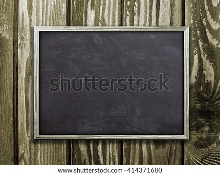 Close-up of one blank blackboard frame on brown wooden boards background