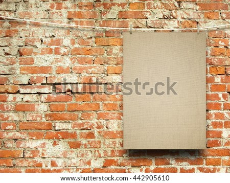 Close-up of one blank brown canvas frame hanged by pegs against orange brick wall background