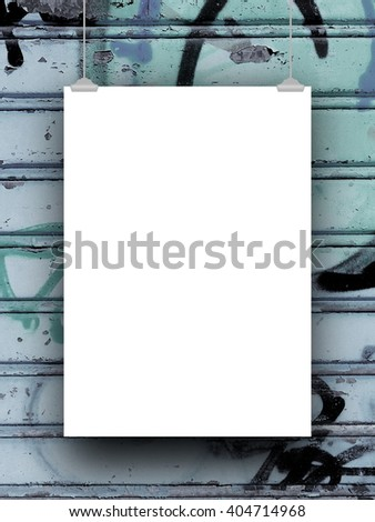 Close-up of one blank frame hanged by clips against blue rusty metal shutter background