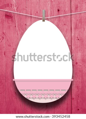 Close-up of one hanged blank Easter egg frame with pink decoration against lilac wooden boards background  - stock photo