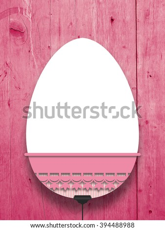 Close-up of one hanged decorated blank Easter egg frame with pink decoration against red wooden boards background - stock photo