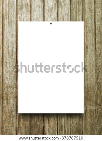 Close-up of one hanged paper sheet frame with nail on brown wooden boards background