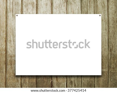 Close-up of one hanged poster paper sheet frame with nails on vertical brown wooden boards background