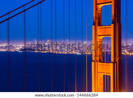 Close up of one post of Golden Gate bridge, and city in the background - stock photo