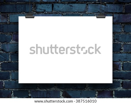 Close-up of one poster paper sheet frame with clips on dark blue brick wall background