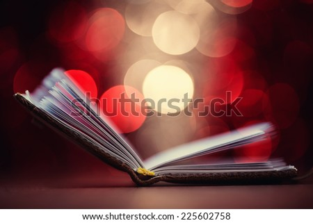 Close up of open book against defocused lights background, shallow depth of field - stock photo