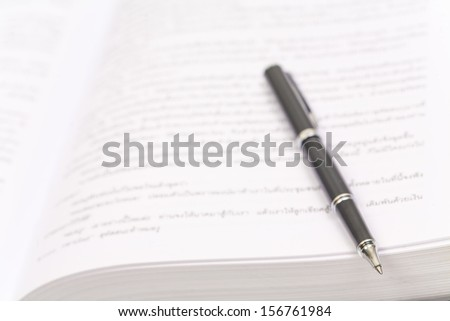 Close-up of open book and pen on white - stock photo