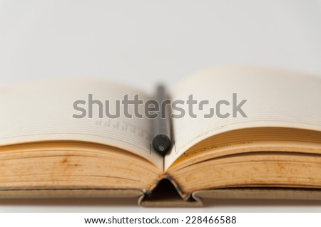 Close-up of open book and pencil - stock photo