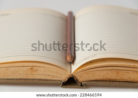 Close-up of open book and pencil