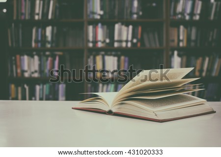 Close up of open book on desk and bookshelf with vintage filter blur background