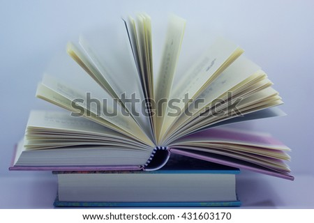 Close up of open book on desk with vintage filter blur background