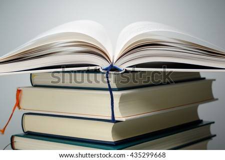 Close up of open book pages on stack of books. Pile of books on gray background.