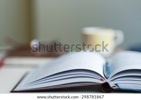 Close up of open notebook blurred with very shallow depth of field (soft focus)