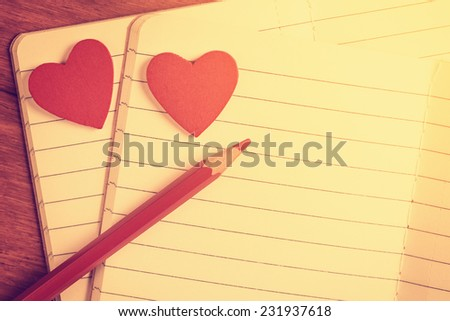 Close up of open notebooks with red hearts and pencil, instagram style toned - stock photo