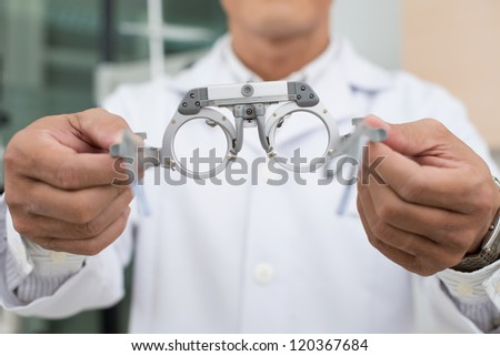 Close-up of optician reaching out glasses to patient - stock photo