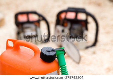 Close up of orange plastic fuel canister with two chainsaws in background - stock photo