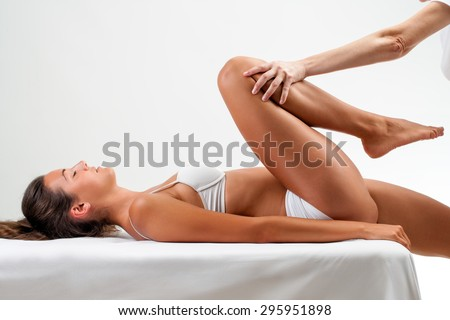 Close up of Osteopath doing healing massage on young woman.Full length portrait of girl laying on back and therapist applying pressure on leg.