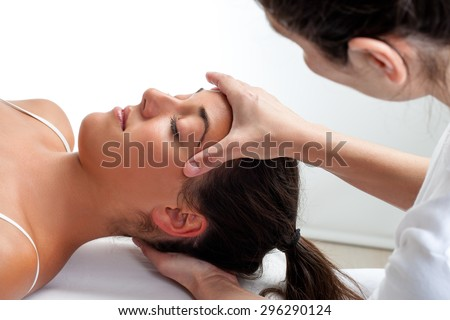 Close up of osteopath doing healing treatment on head. Hands doing massage on front and back of head. - stock photo