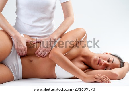 Close up of osteopath doing manipulative visceral massage on young woman.Therapist pressing visceral nervous system on stomach. - stock photo