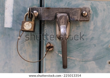 Close up of padlock and old metal hasp and staple on an metal door & hasp And Staple\