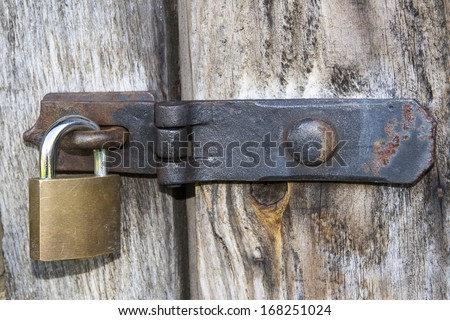 Close up of padlock and old metal hasp and staple on an old wooden door - stock photo