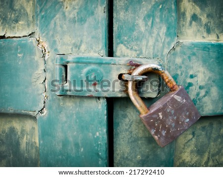 Close up of padlock and old metal hasp and staple on an vintage wooden door - stock photo