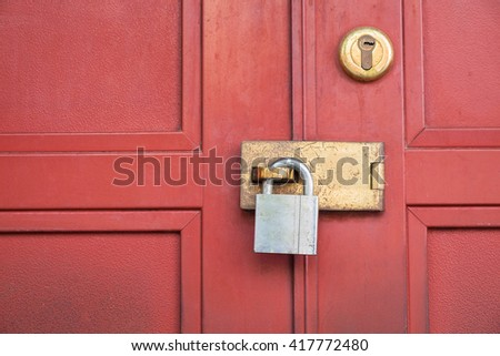 Close up of padlock and old metal hasp on a red vintage wooden door. - stock photo