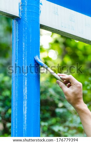 Close-up of paint job with blue paint brush outside - stock photo