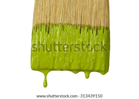 close up of paintbrush dripping green paint isolated over white background