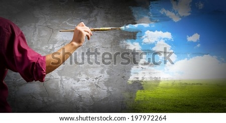 Close up of painter's hand with brush - stock photo