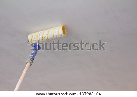Close up of painting a ceiling with roller - stock photo