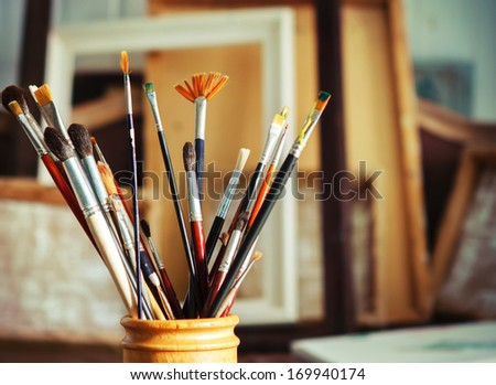 Close up of painting brushes in studio of artist. Tones picture - stock photo