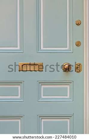 Close Up of Pale Blue Front Door with White Surrounding Door Frame and Windows - stock photo