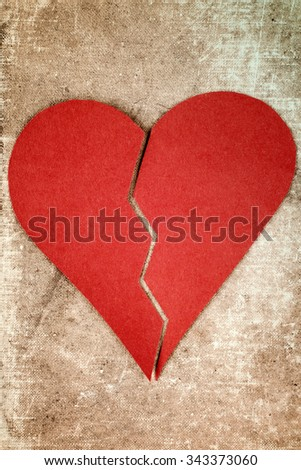 Close up of paper broken heart on blue background