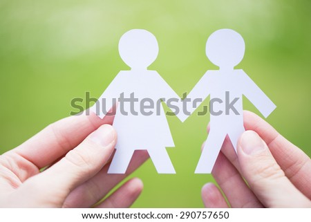 close up of paper people couple held in woman hands on natural, green background - stock photo