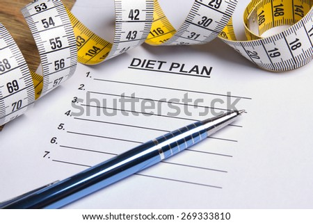 close up of paper with diet plan, pen and yellow measure tape - stock photo