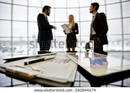 Close-up of papers and touchpad on table against managers - stock photo