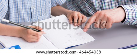 Close-up of parent helping his child with homework
